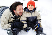 Father and son playing happily in snow, winter season — Stock Photo
