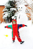 Kid playing happily in snow making snowman, winter season — Stock Photo