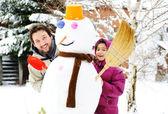 Pai e filha, pai e menina que joga o jogo com o homem de neve, inverno, decem — Foto Stock