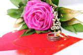 Love rose, for lover, on white with affiance (marriage) rings and red heart — Stock Photo