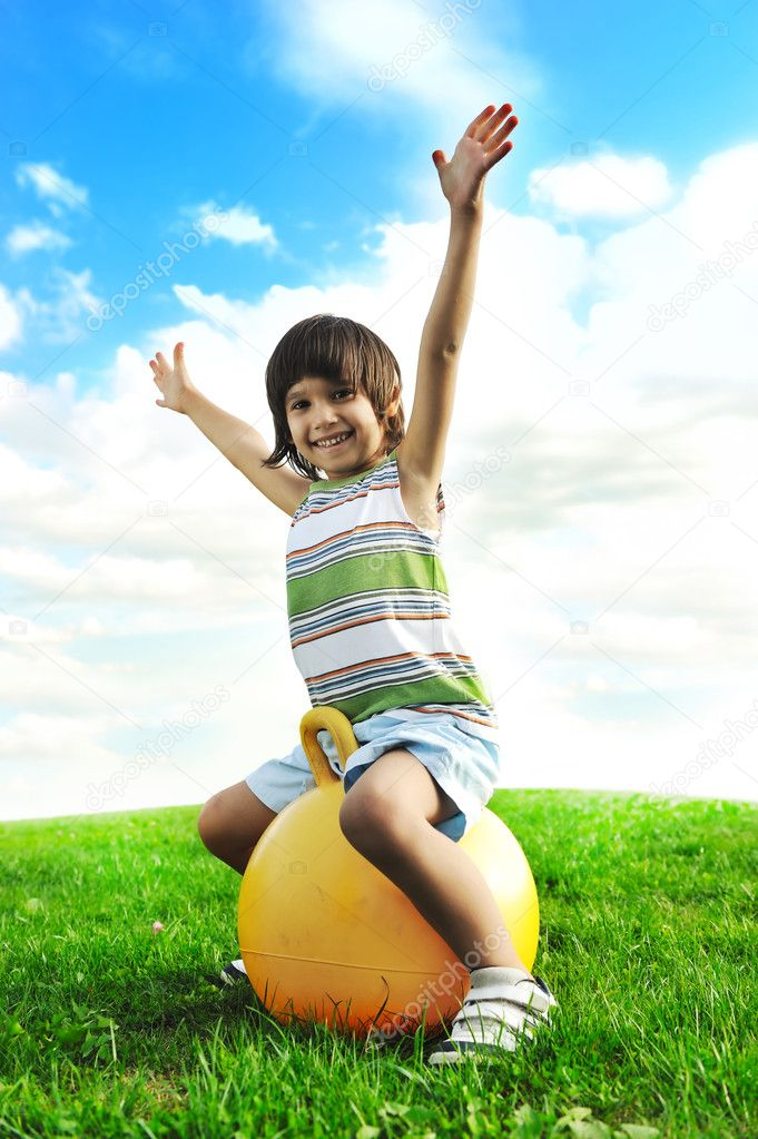 Sporty cute positive kid, playing happily with big ball on green meadow — Stock Photo #6150388