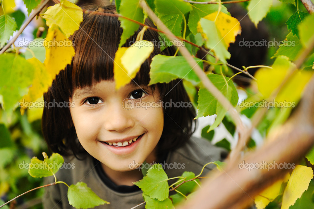 Happy childhood outdoor, happy faces between the leaves of the trees in forest or park, look for more in my porftolio — Stock Photo #6150615