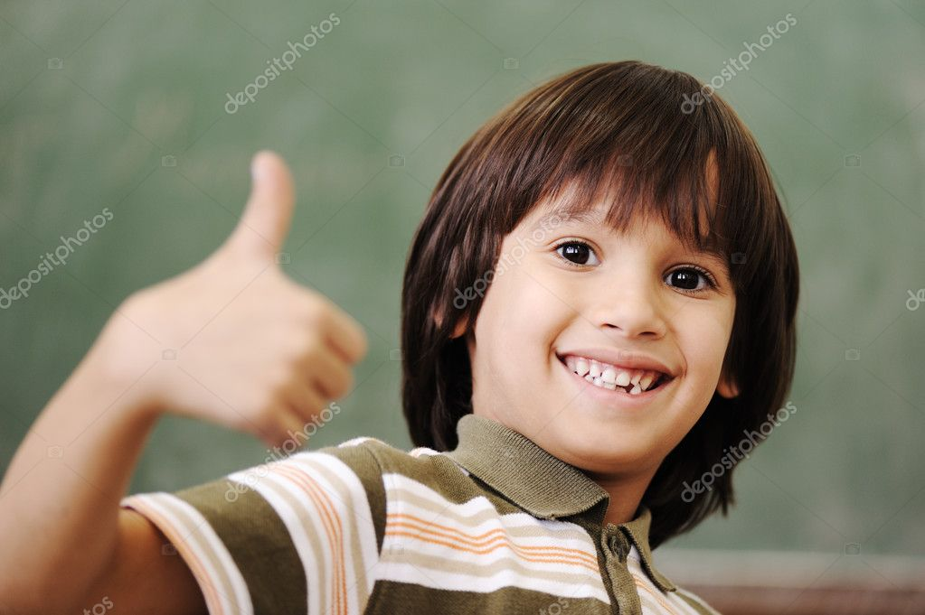 Happy boy in classroom with thumb up: green board behind — Stock Photo #6150655