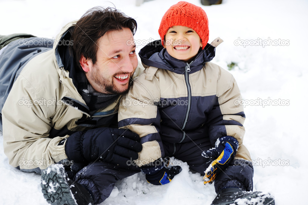 Father and son playing happily in snow, winter season  Stock Photo #6151365