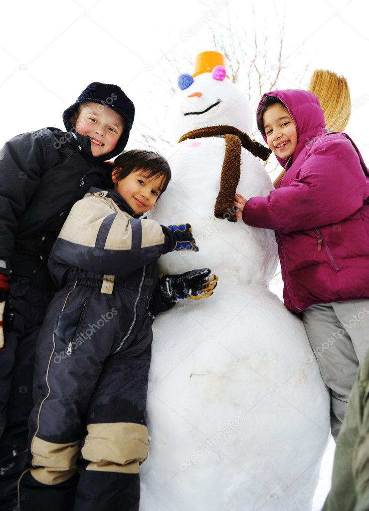 Group of children playing happily in snow making snowman, winter season — Stock Photo #6151373
