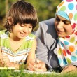 Muslim mother and her little son learning together laying on ground — Stock Photo