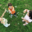 Stock Photo: Small group of happy children making bubbles and playing together in nature