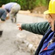 Elderly menager on workplace with workers on fresh concrete - Stock Photo