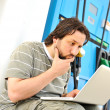 Stock Photo: Mwith laptop on gas station with silly expression on his face after read