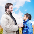Young father helping his son with fall - winter clothes outdoor, happy scen — Stock Photo
