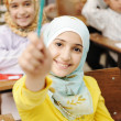 Adorable Muslim girl in classroom with her friends children students — Stock Photo #6187680