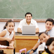 Foto de Stock  : Happy young teacher and children in classroom together