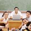 Happy young teacher and children in classroom together - Stock Photo