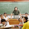 Teacher in classroom with his little happy students — Stock Photo