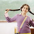 Gorgeous girl holding her hair and standing in classroom in front of board — Stock Photo