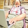 Full length of a senior woman sitting and using a laptop against — Stock Photo