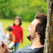 Young relaxed father reading book and children playing around — Stock Photo