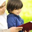 Foto Stock: Mother Muslim and her son in nature, reading together