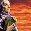 Adorable Muslim girl holding holy book Koran, against red sky — Stock Photo #6187972