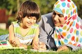 мусульманские мать и маленький сын обучения вместе лежащие на земле — Стоковое фото