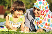 Mãe muçulmana e seu pequeno filho aprendendo juntos, deitado no chão — Foto Stock