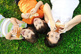 Three children laying on green grass on ground and eating sandwiches and sm — Foto de Stock