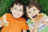 Dois rapazes giros deitado no chão na natureza e felizes de comer alimentos saudáveis — Foto Stock