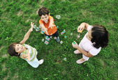 Small group of happy children making bubbles and playing together in nature — Stock Photo