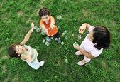 Liten grupp av glada barn att göra bubblor och spela tillsammans i naturen — Stockfoto