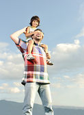 Young father and his son on back, piggyback, pikaboo playing, outdoor scene — Stok fotoğraf
