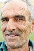 Face portrait of a wrinkled cheerful smiling senior man — Stock Photo