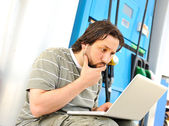 Man with laptop on gas station with silly expression on his face after read — Foto de Stock