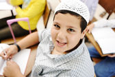Very positive kid with white small hat sitting on desk in classroom and smi — Stock Photo