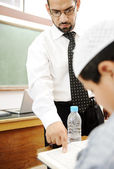Young teacher helping a student in classroom — Stock Photo