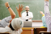 Good teacher in classroom in front of the board — Stock Photo