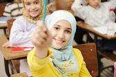 Adorable Muslim girl in classroom with her friends children students — Stock Photo