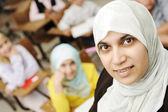Muslim female teacher in classroom with children pupils (students) — Stock Photo