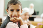 Positive kid in classroom smiling and looking in camera — Stock Photo
