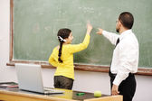 Teacher helping schoolgirl in front of board — Stock Photo
