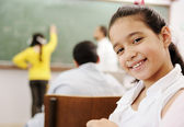 Adorable girl smiling in school classroom and behind her class activities — Stock Photo