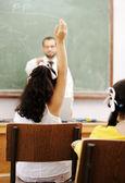 Teacher and pupil in school, hand rising and answering — Stock Photo