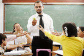 Young male teacher with children in modern school, activities — Stock Photo
