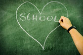 Child drawing and writing on board: heart and school — Stock Photo