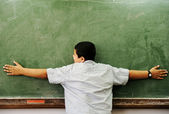 Schoolchild hugging board in classroom — Stock Photo