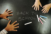 Multiraces children hands on blackboard with chalks: back to school! — Photo