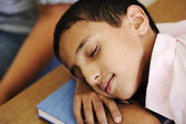 Kid in classroom on desk falling asleep on his notebook — Stock Photo