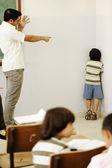 Castigar a los niños en clase, profesor enojado y chico en esquina — Foto de Stock