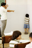 Punishing children in classroom, angry teacher and kid in corner — Stock Photo