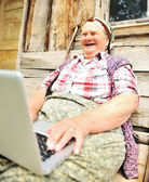 Senior aged woman with laptop — Stock Photo