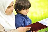 Mãe muçulmana e seu filho na natureza, ler juntos — Foto Stock